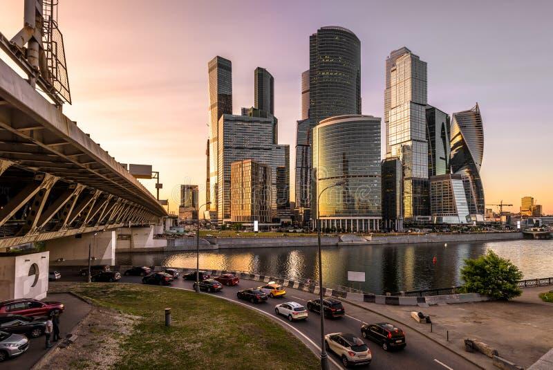 Moskou-stad wolkenkrabbers en brug over Moskva-Rivier bij zonsondergang, Rusland royalty-vrije stock afbeeldingen