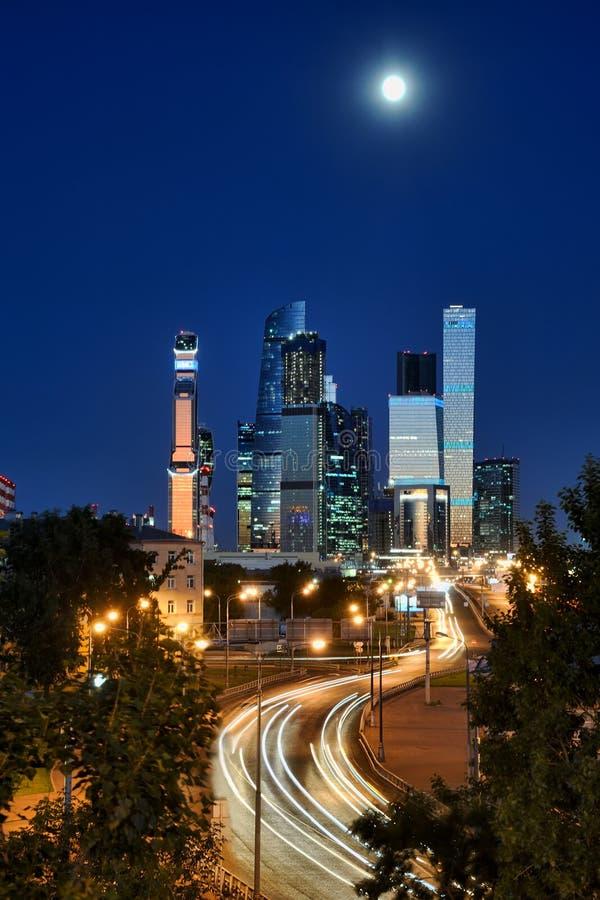 Moskva城市摩天大楼和汽车光足迹在月光下 免版税库存图片