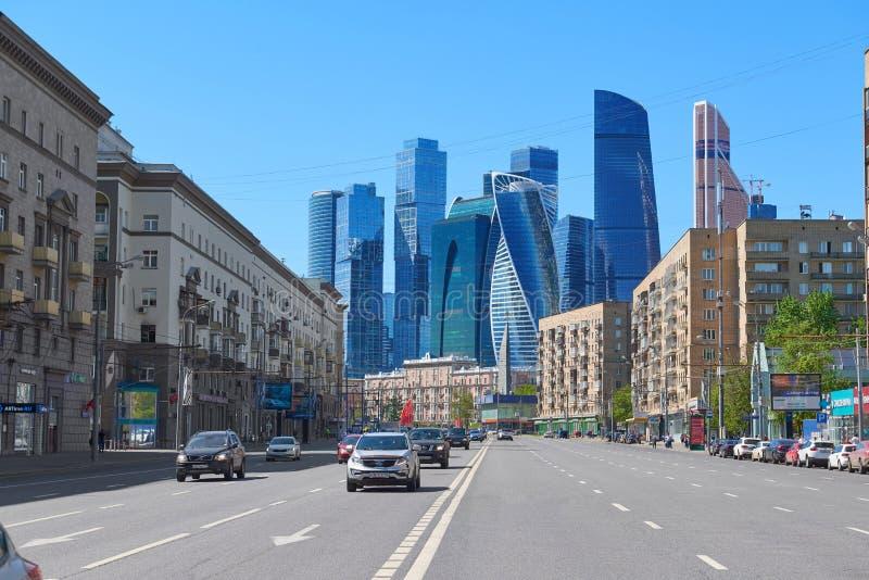 MOSKVA MAJ, 9, 2018: Perspektivsikten av stadsbilvägen bland byggnader och shoppar med mitten för kontoret för Moskvastadsaffären royaltyfria foton