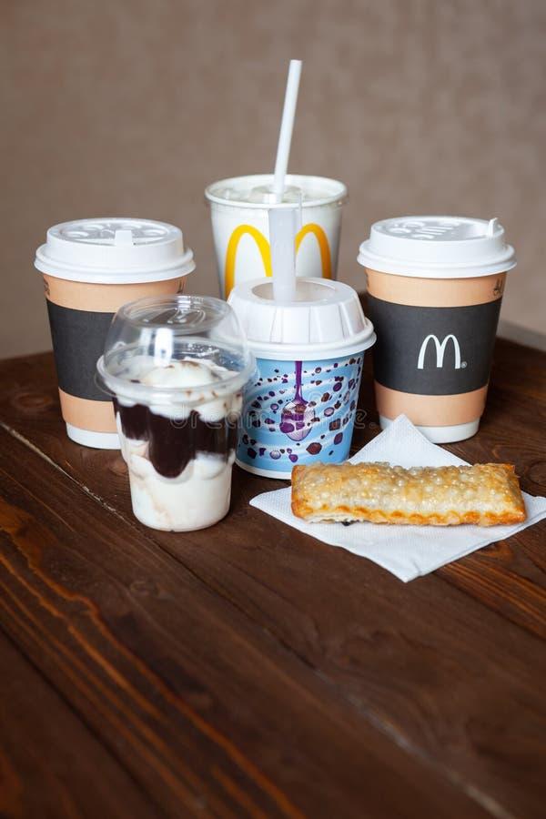 Moskva Ryssland - April 06, 2019: Mcdonald matleverans Efterrätter och varma drinkar på trätabellen Närbild Slapp fokus vertikalt royaltyfri fotografi