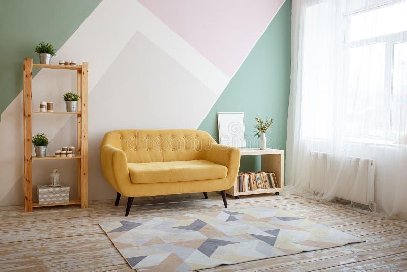 Moskva Ryssland, april 7th 2019: Trevlig vardagsrum med soffan, matta, gr?n v?xt p? en bokhylla royaltyfri fotografi