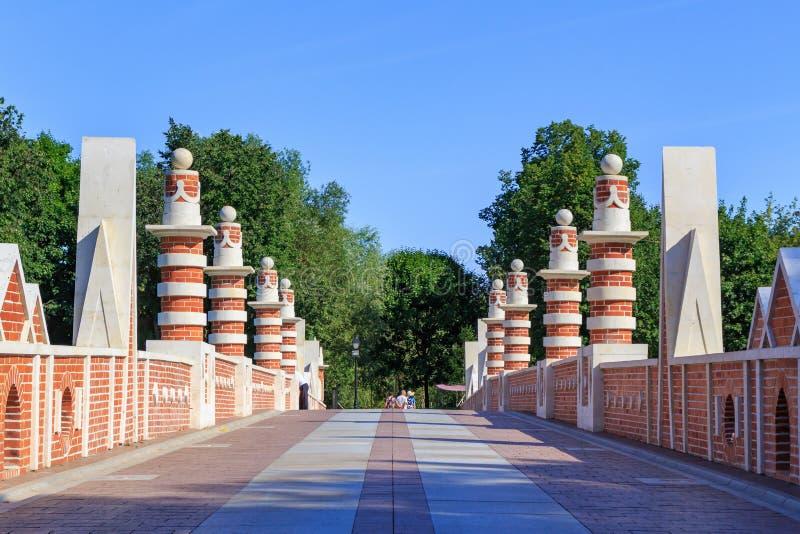 Moskva Ryssland - Augusti 12, 2018: Sikt av vandringsledet på den stora bron över ravin i Museum-reserven Tsaritsyno mot blå himm arkivfoto