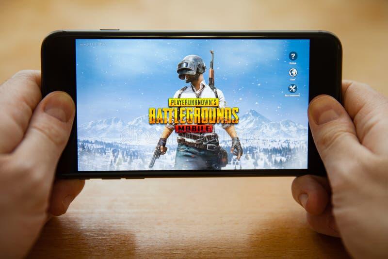 Moskva/Ryssland - Februari 24, 2019: ladda pubg spela på en svart smartphone i manliga händer royaltyfria bilder