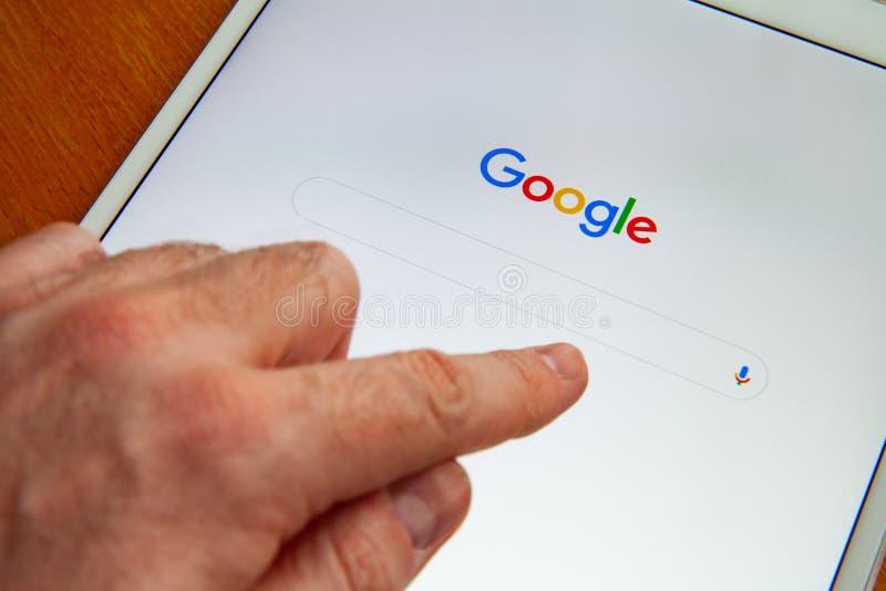 Moskva/Ryssland - Februari 25, 2019: Vit ipad ligger på tabellen Google söker skärmen arkivbild