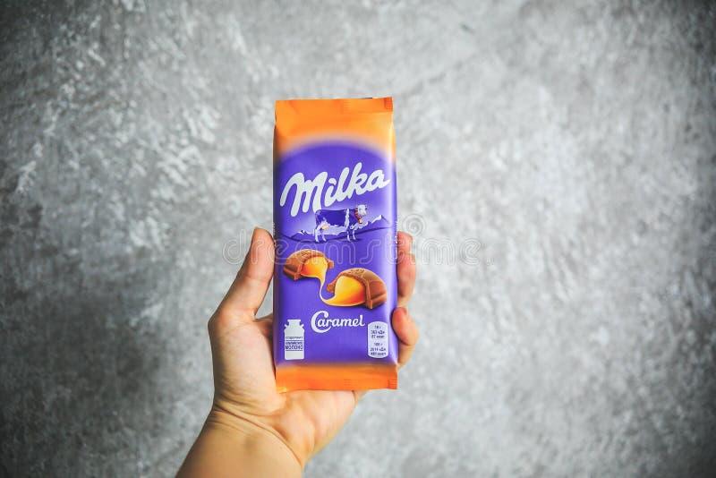 MOSKVA RYSSLAND - JULI 5, 2019: Alpina Milka mjölkar chokladstången med karamell som marknadsföras av Mondelez International Milk royaltyfria foton