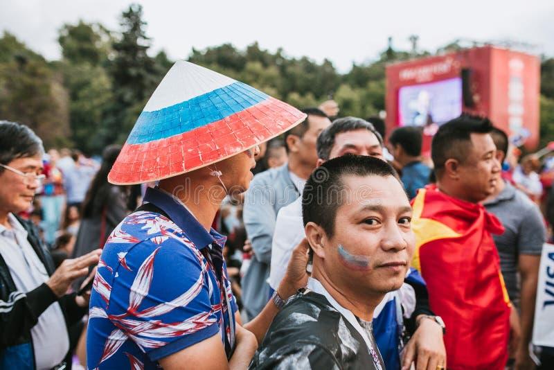 MOSKVA RYSSLAND - JULI 2018: Asiatiska fans i vietnamesiska hattar som målas i färgerna av den ryska flaggan i fanzonen under Wor arkivbild