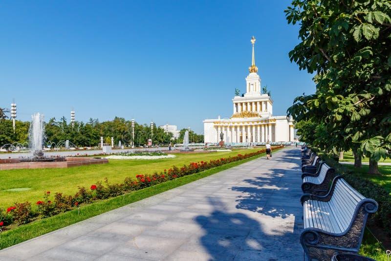 Moskva Ryssland - Juli 22, 2019: Bänkar under gröna träd på gränden i VDNH parkerar på den soliga sommarmorgonen VDNH är populärt royaltyfri fotografi