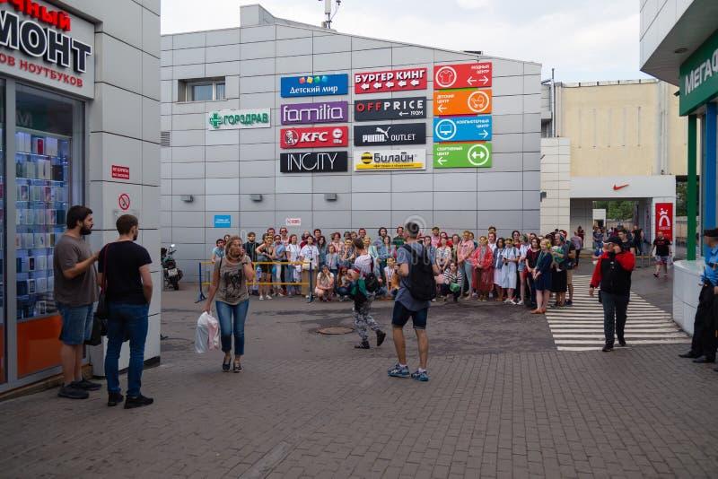 MOSKVA RYSSLAND - JULI 22, 2018: En grupp av ungdomari mång--färgat hörlurarSONY H öra som samlas på för sökandeparti arkivbild