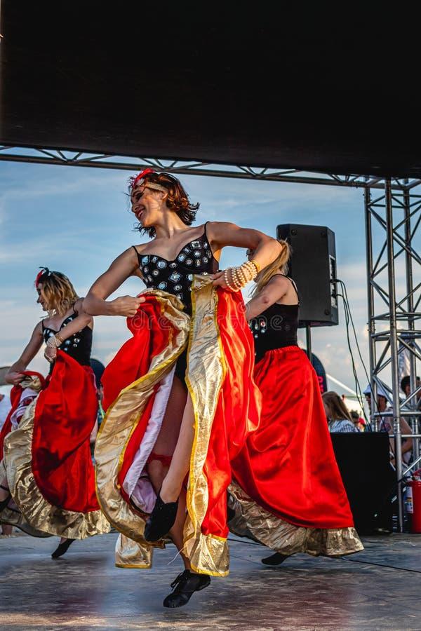 MOSKVA RYSSLAND - JULI 27, 2019: Grupp av kvinnor i röda klänningar som dansar på den JohnCalliano vattenpipafesten arkivfoton