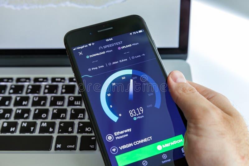 Moskva/Ryssland - Juli 13, 2019: Svart iPhone 8 plus i handen på bakgrunden av MacBook På-skärm program SpeedTest royaltyfri fotografi