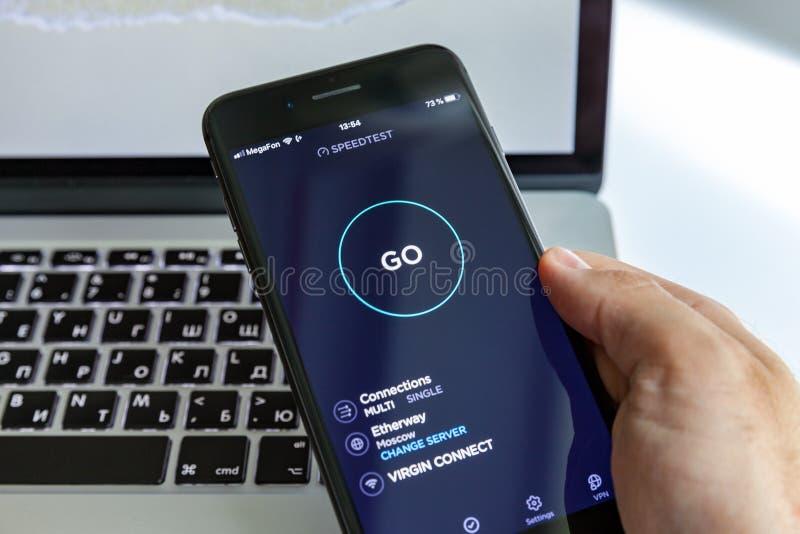 Moskva/Ryssland - Juli 13, 2019: Svart iPhone 8 plus i handen på bakgrunden av MacBook På-skärm program SpeedTest arkivfoton