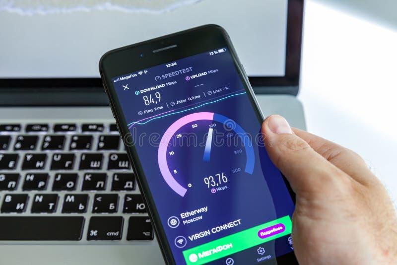 Moskva/Ryssland - Juli 13, 2019: Svart iPhone 8 plus i handen på bakgrunden av MacBook På-skärm program SpeedTest arkivbilder