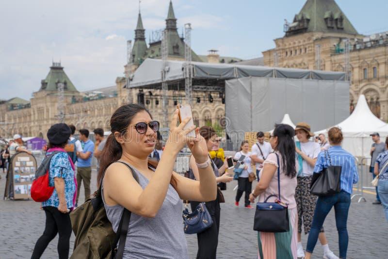 MOSKVA RYSSLAND - JUNI 04, 2019: En kvinnlig turist tar bilder på hennes smartphonesikt på röd fyrkant i Moskva arkivbilder