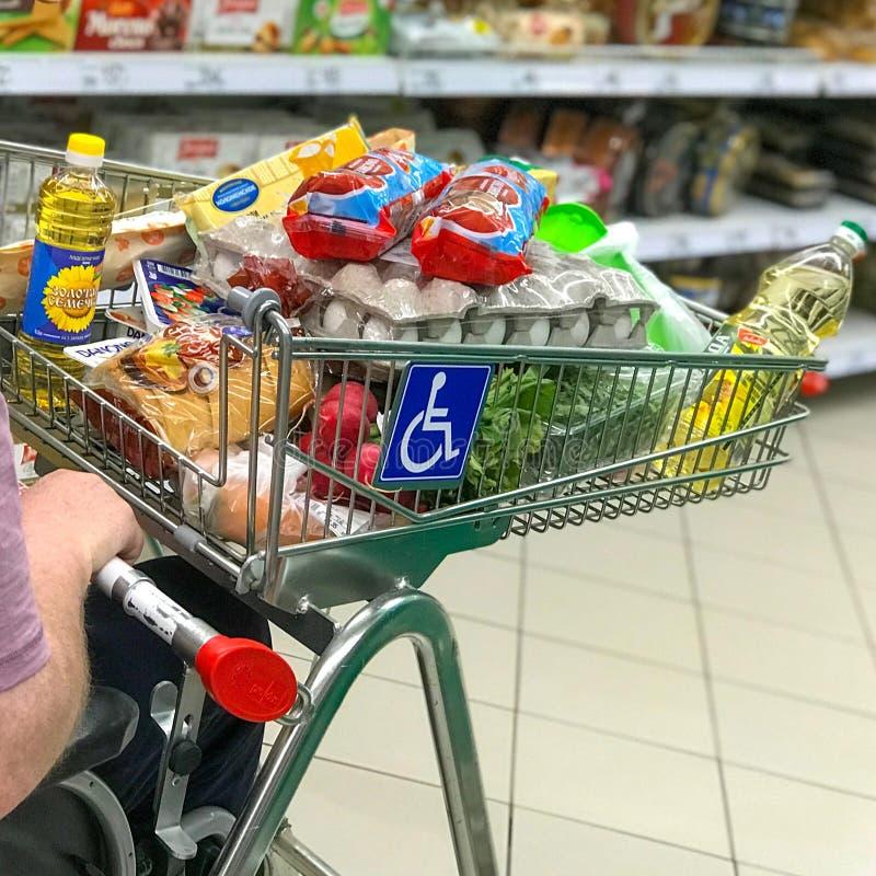 MOSKVA RYSSLAND - JUNI 10, 2019: Rörelsehindrad man som använder en rullstol med en Shooping vagn i den Auchan supermarket access royaltyfria bilder