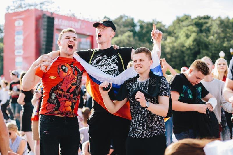 MOSKVA RYSSLAND - JUNI 2018: Tre ryska fans är lyckliga och banhoppningen med nationsflaggan i fanzonen under världscupen royaltyfri foto