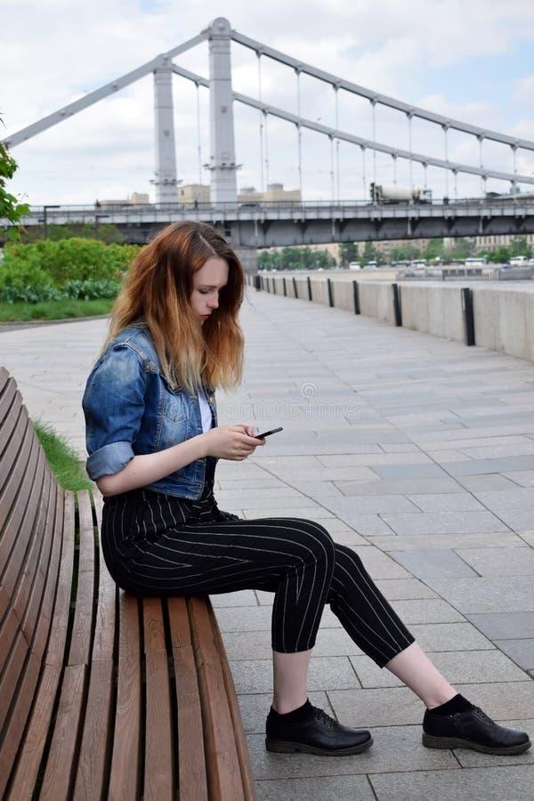 Moskva Ryssland - Maj 13, 2019: Den unga kvinnan ser in i hennes smartphone på den Krymskaya invallningen royaltyfri bild