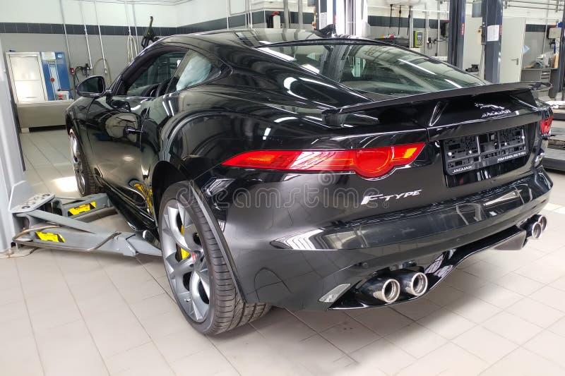 Moskva Ryssland - Maj 1, 2019: Inre av svart Jaguar F-typ R p? en elevator p? en Land Rover servicemitt Reparation och diagnostik royaltyfria bilder