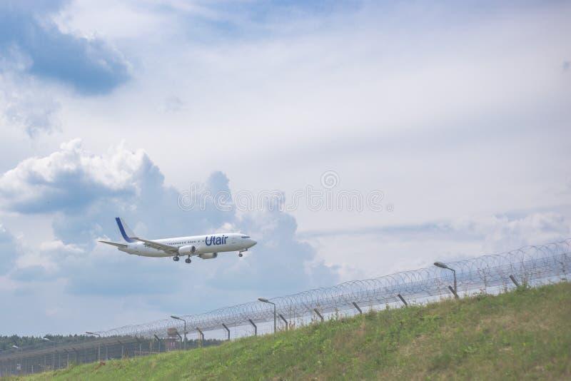 Moskva Ryssland - 9 Maj 2019: N?rbild av en Utair f?r flygbolag f?r passagerareniv? landning p? flygplatsen mot p? bakgrunden av  arkivfoton