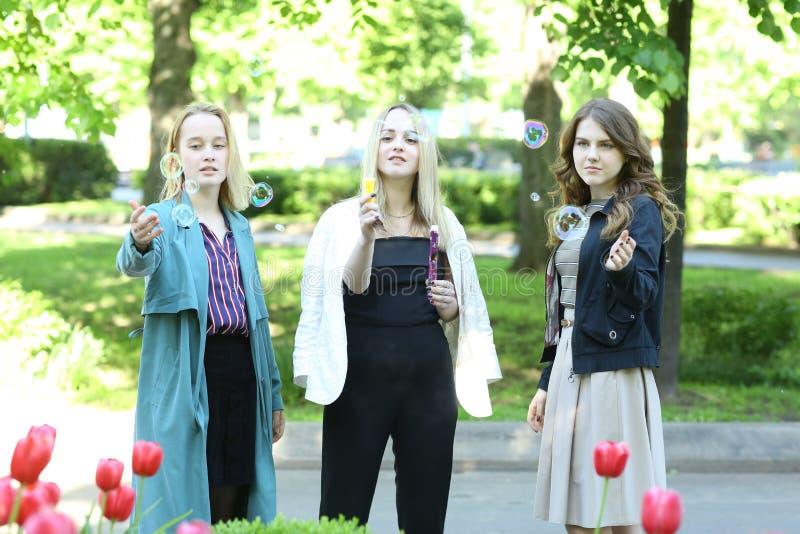 Moskva, Ryssland, maj 22019: Skoleleverna deltar på högtidliga högskolepromédagen och spelar med tvålbubblor i parken i royaltyfri bild