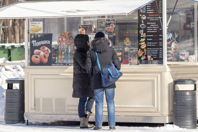 MOSKVA RYSSLAND - MARS 02, 2019: En köpande gatasnabbmat för par i stannar under promenaden i en stad parkerar i vintern som äter royaltyfri bild