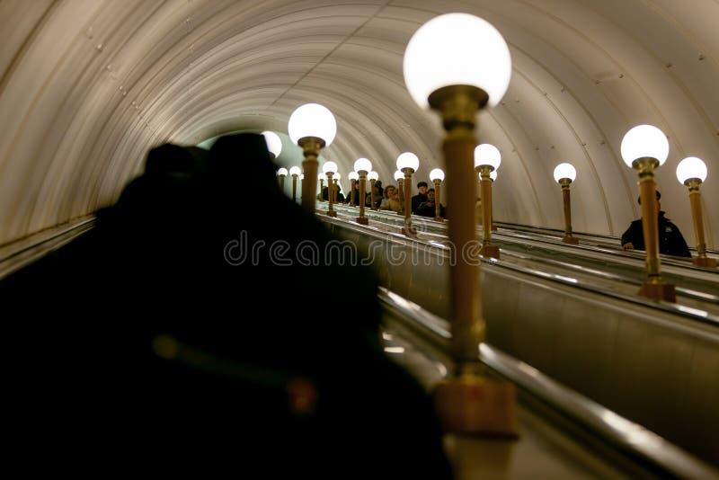 MOSKVA RYSSLAND - MARS 12, 2018: Folket stiger ned till gångtunnelen på en rulltrappa på tunnelbanastationen Prospekt Mira, en ri royaltyfri bild