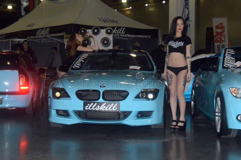 Moskva som trimmar modeller för show 2015, poserar bredvid den blåa BMW royaltyfri foto