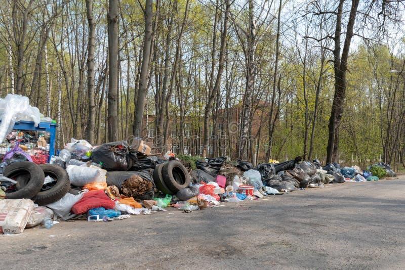 Moskvaregion, Ryssland - April 26, 2019: Olaglig avskr?def?rr?dsplats p? v?grenen Sommarinv?nare kastar avfall l?ngs v?gen royaltyfri bild