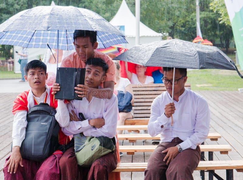 Moskwa, Rosja, 04 august 2018 Niewiadomego balijczyka młodego faceta chuje od deszczu pod parasolem przy festiwalem Indonezja fotografia stock