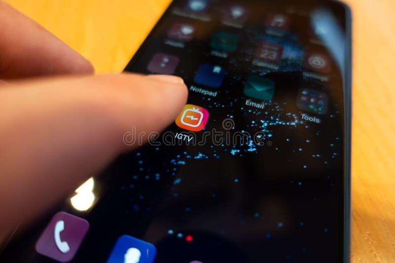 Moskwa Rosja, Czerwiec, - 23, 2018: Instagram IGTV Mężczyzna naciska guzika telefon IGTV Ikony IGTV zbliżenie editorial obrazy stock