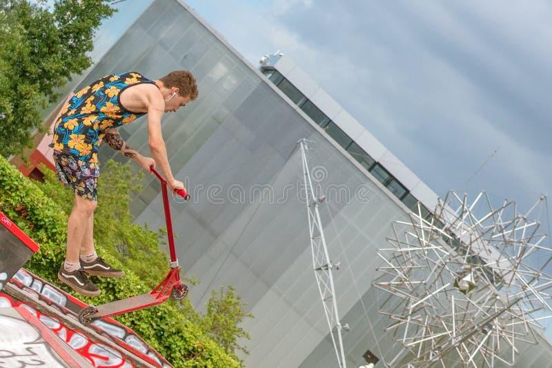 Moskwa Rosja, Czerwiec, - 21, 2018: Młody człowiek z hulajnogi doskakiwaniem obrazy stock