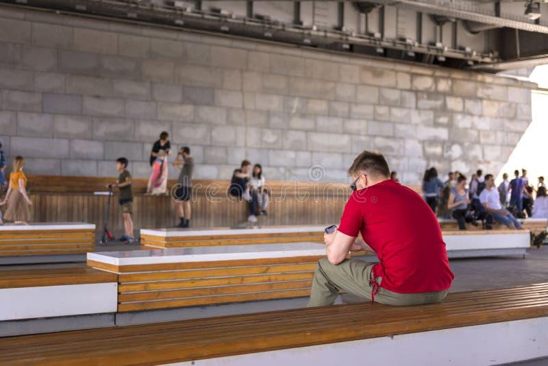 Moskwa, Rosja, 02 2019 Czerwiec Młody faceta obsiadanie na ławce pod mostem obrazy stock