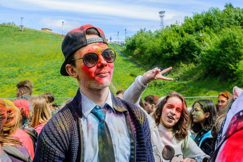 Moskwa Rosja, Czerwiec, - 3, 2017: Portret młody facet w okularach przeciwsłonecznych z czerwoną twarzą w farbie przy lato festiw fotografia royalty free