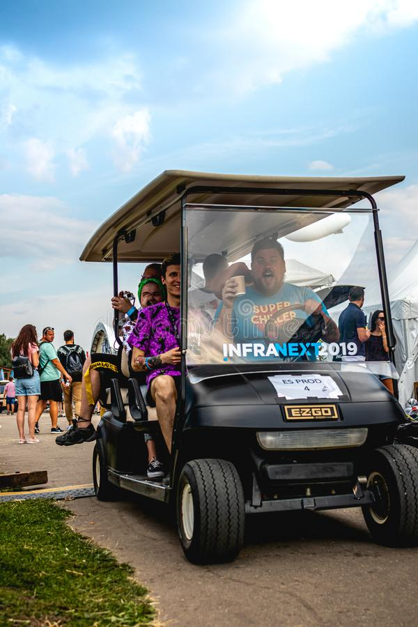 MOSKWA ROSJA, LIPIEC, - 27, 2019: Ludzie w golfowym samochodzie przy JohnCalliano nargile fest powozika samochodem obrazy stock