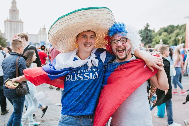 MOSKWA ROSJA, LIPIEC, - 2018: Rosyjski i Francuski piłki nożnej fan w sambrero z flaga w fan strefie podczas światu i fotografia royalty free