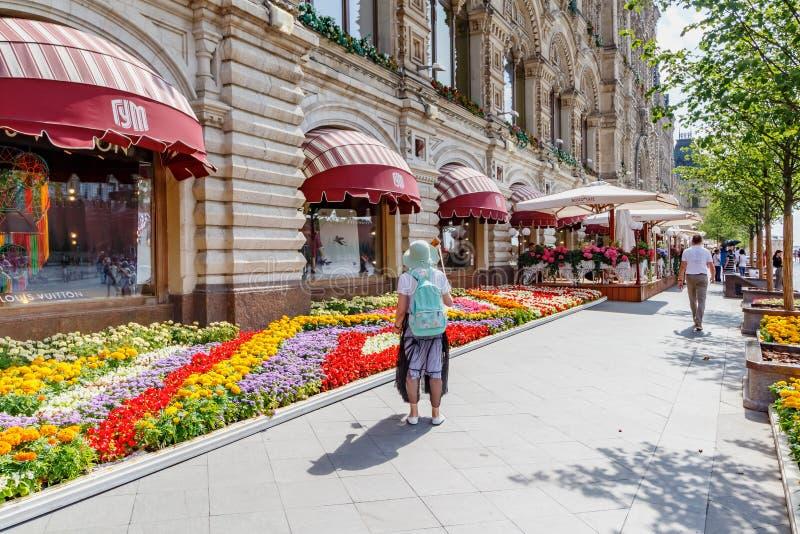 Moskwa Rosja, Lipiec, - 28, 2019: Turysta bierze fotografię przeciw dekoruje kwiatu departament stanu GUMOWYM sklepem na placu cz zdjęcie stock