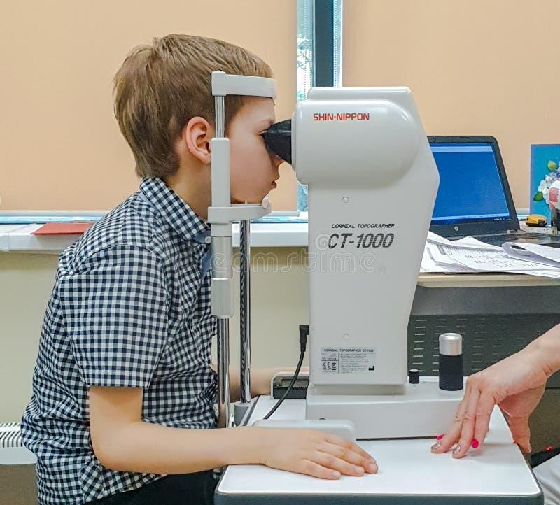 Moskwa Rosja, Maj, - 20, 2019: Chłopiec przy spotkaniem z oftalmologiem sprawdza wzrok na przyrządzie Zdrowie dziecka fotografia stock