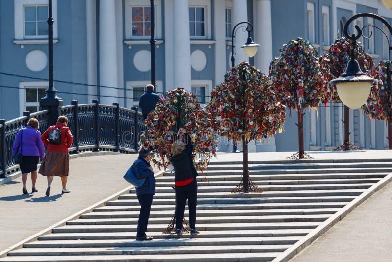 Moskwa Rosja, Maj, - 01, 2019: Mężczyzna i kobieta wieszamy kłódkę na drzewie miłość na Tretyakovskiy mostu Luzhkov moście wewnąt zdjęcia stock