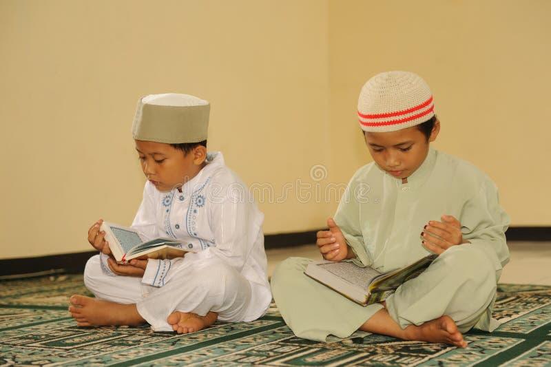 Moslem scherzt das Lesen von Koran stockfotografie