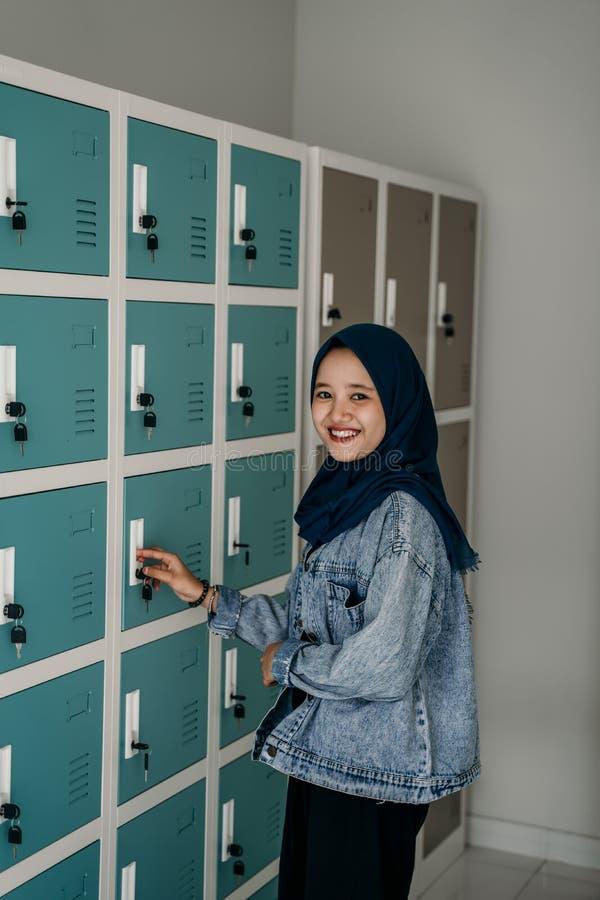 Moslemische asiatische Studentin im Umkleideraum lizenzfreie stockfotos