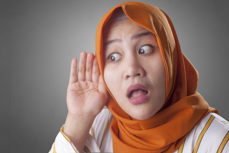 Moslemische Dame, wenn Sie sorgf?ltig, Hand auf Ohr h?ren lizenzfreie stockbilder