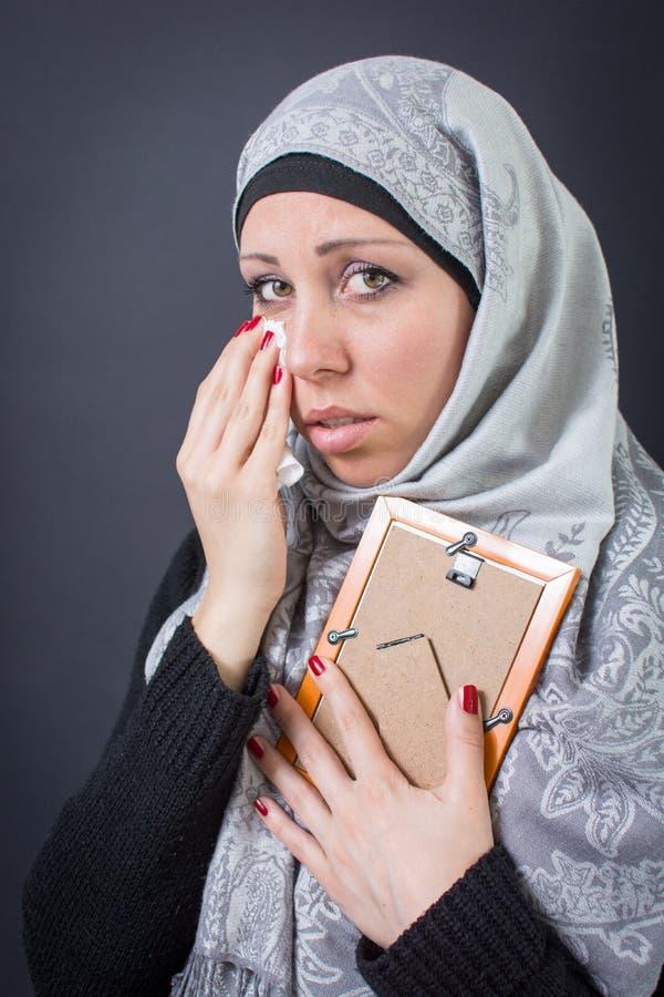 Moslemische Frau, die über einer Fotografie ächzt lizenzfreies stockbild