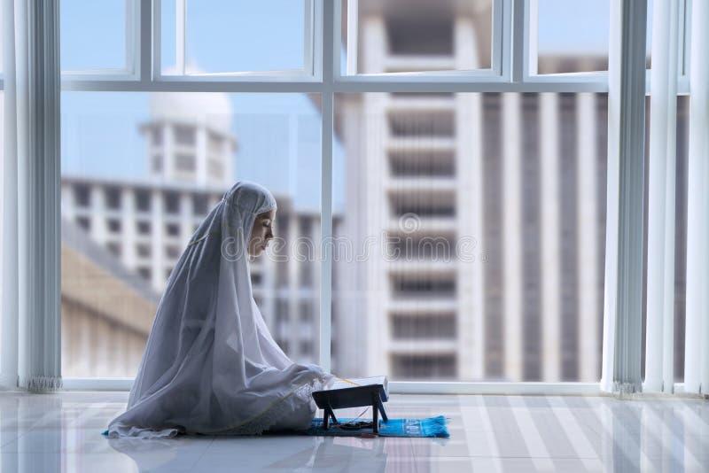 Moslemische Frau, die den Quran in der Moschee liest stockbilder