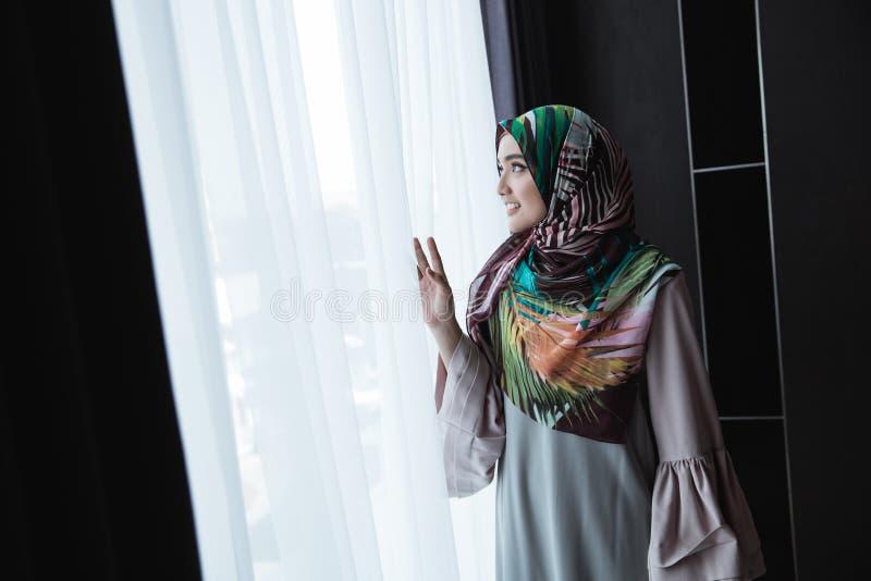 Moslemische Frau, die heraus das Fenster schaut lizenzfreie stockfotografie