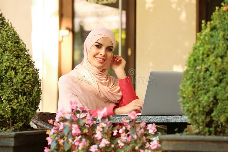 Moslemische Frau, die Laptop verwendet stockfotos