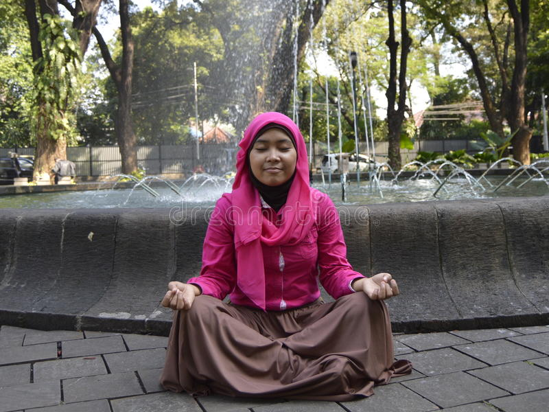 Moslemische Frau, die am Park meditiert stockbilder