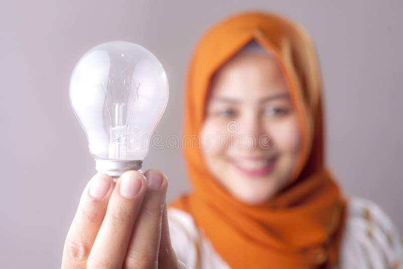 Moslemische Frau hält Lampen-Birne stockfotos