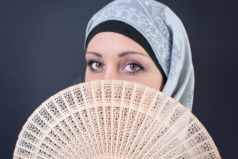 Moslemische Frau hinter einem Handfan stockfotos