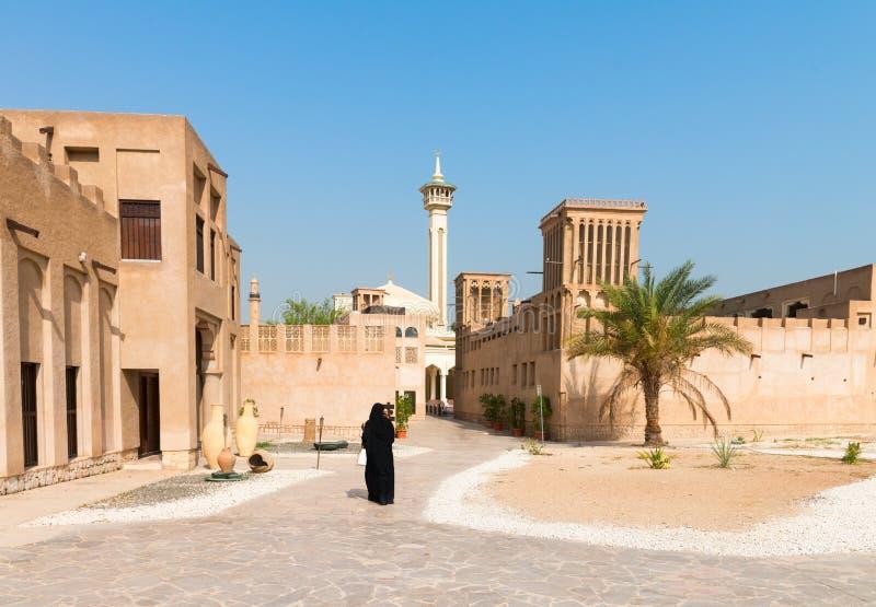 Moslemische Frau im alten arabischen Bezirk mit Moschee lizenzfreies stockbild