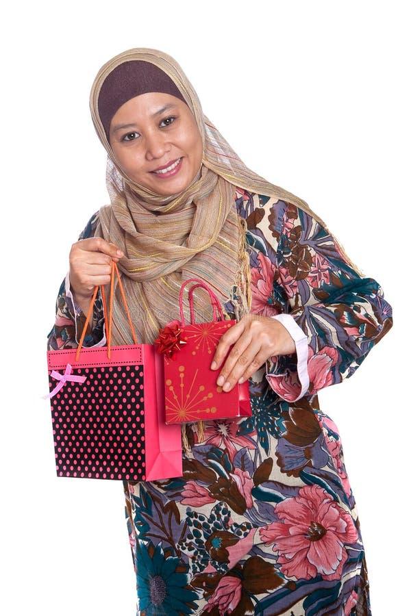 Moslemische Frau mit hell farbigen Einkaufenbeuteln lizenzfreies stockfoto