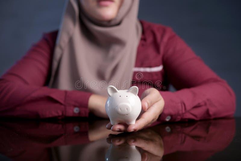 Moslemische Frau mit Sparschwein, Rettungsinvestitions-Konzept stockfoto